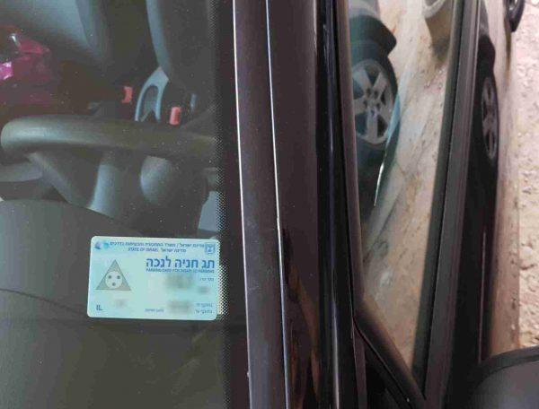דוגמה לשימוש במחזיק. מתלה תו נכה לרכב עם כרטיס בצילום מרחוק